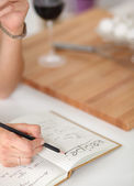 Happy beautiful woman standing in her kitchen writing on a notebook at home — Stock Photo