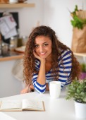 Smiling young woman with coffee cup and laptop in the kitchen at home — Foto de Stock