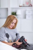 Woman sitting on a sofa in her house with camera — Stock Photo