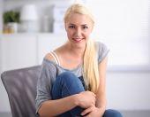 Joven hermosa mujer sentada en el sofá en la sala de — Foto de Stock