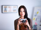 Young woman watching footage on film, standing near window — Stock Photo