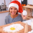 Happy young woman smiling happy having fun with Christmas preparations wearing Santa hat — Stock Photo #59126067