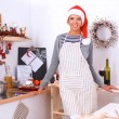 Happy young woman smiling happy having fun with Christmas preparations wearing Santa hat — Stock Photo #59126071