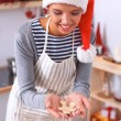 Happy young woman smiling happy having fun with Christmas preparations wearing Santa hat — Stock Photo #59126073