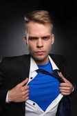 Young businessman acting like a super hero and tearing his shirt, isolated on gray background — Stock Photo