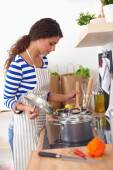 Young woman in the kitchen preparing a food — Stockfoto