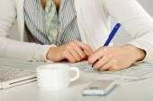 En kvinna på skrivbord skriva på ett papper, isolerad på vit — Stockfoto