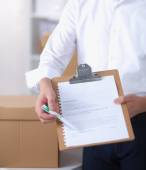 Delivery man with  parcel and a tablet standing in office — Stock Photo