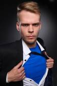 Young businessman acting like a super hero and tearing his shirt, isolated on gray background — Stok fotoğraf