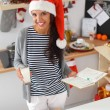 Happy young woman smiling happy having fun with Christmas preparations wearing Santa hat — Stock Photo #62321651