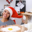 Happy young woman smiling happy having fun with Christmas preparations wearing Santa hat — Stock Photo #62321673