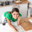 Happy beautiful woman standing in her kitchen writing on a notebook at home — Stock Photo #62321853