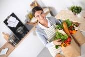 Woman with shopping bags in the kitchen at home, standing near desk — Stock Photo