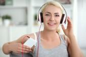 Joven mujer hermosa en casa sentado en el sofá y escucha música — Foto de Stock