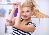 Beautiful young stylist near rack with hangers in office — Foto Stock