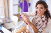Beautiful young stylist woman near rack with hangers — Foto Stock