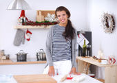 Smiling young woman in the kitchen, on christmas background — Stock Photo