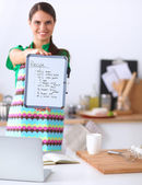 Smiling young woman in the kitchen, on  background — Stock Photo