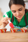 Young woman is making cakes in the kitchen — Stock Photo
