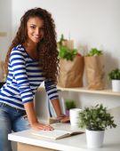 Leende ung kvinna i köket, isolerad på bakgrunden — Stockfoto