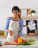 Verdure di taglio giovane donna in cucina — Foto Stock