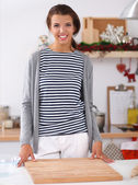 Smiling young woman in the kitchen, on christmas background — Stok fotoğraf