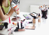 Young beautiful woman making make-up near mirror,sitting at the desk — Foto de Stock
