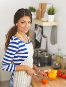 Young woman cutting vegetables in kitchen, standing near desk — Foto Stock