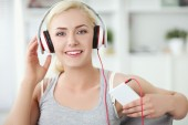 Young beautiful woman at home sitting on sofa and listening music — Foto Stock