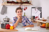 Na boże narodzenie tło uśmiechający się młoda kobieta w kuchni, tle — Fotografia Stock