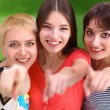 Three happy girls pointing fingers at you choosing — Stock Photo #67655477