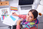 Young attractive female fashion designer working at office desk, drawing while talking on mobile — Stock Photo