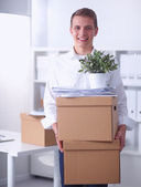 Portrait of a person with moving box and other stuff isolated on white — Stock Photo