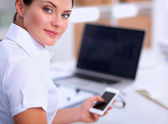 Businesswoman sending message with smartphone sitting in the office — Stock Photo