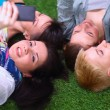 Four young women lying on green grass with mobile phone — Stock Photo #68830263