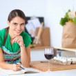 Happy beautiful woman standing in her kitchen writing on a notebook at home — Stock Photo #68832597