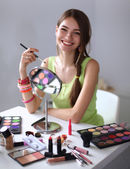 Young beautiful woman making make-up near mirror,sitting at the desk — Stok fotoğraf