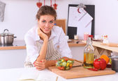 Smiling young woman in the kitchen — Stock Photo