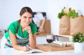 Gelukkig mooie vrouw permanent in haar keuken schrijven op een laptop thuis — Stockfoto