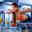 Sports young woman doing exercises on trainer back machine in the gym — Stock Photo #69593855