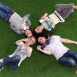 Four young women lying on green grass with mobile phone — Stock Photo #69594779