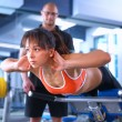 Beautiful woman at the gym exercising with her trainer — Stock Photo #70198183