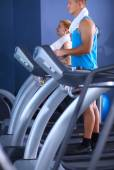 Group of people at the gym exercising on cross trainers — Stock Photo