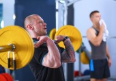 Bodybuilder with barbell in gym — Stock Photo