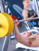 Young man lifting the barbell in gym with instructor — Foto Stock