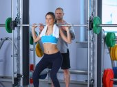 Beautiful woman at the gym exercising with her trainer — Stock Photo