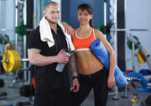 Young man and woman relaxing in sports outfits at the gym — Stock Photo