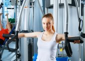 Beautiful girl at the gym exercising on trainers — Stock Photo
