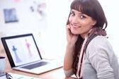 Portrait of attractive female fashion designer sitting at office desk — Stock Photo
