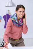Giovane attraente femmina stilista lavorando alla scrivania ufficio, disegno mentre parla mobile — Foto Stock